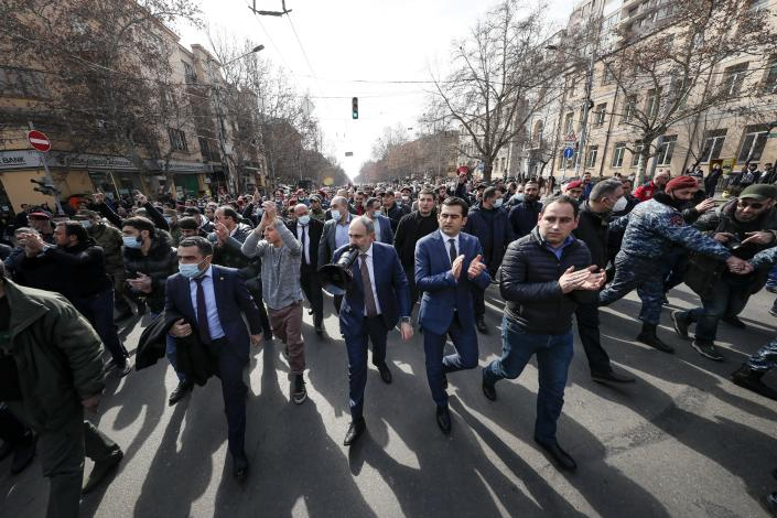 Armenian Prime Minister Nikol Pashinyan, center, surrounded by his supporters, speaks through a loudspeaker during a rally in the central in Yerevan, Armenia, Thursday, Feb. 25, 2021. Armenia's prime minister accused top military officers on Thursday of attempting a coup after they demanded he step down, adding fuel to months long protests calling for his resignation following the nation's defeat in a conflict with Azerbaijan over the Nagorno-Karabakh region. (Tigran Mehrabyan/PAN Photo via AP)