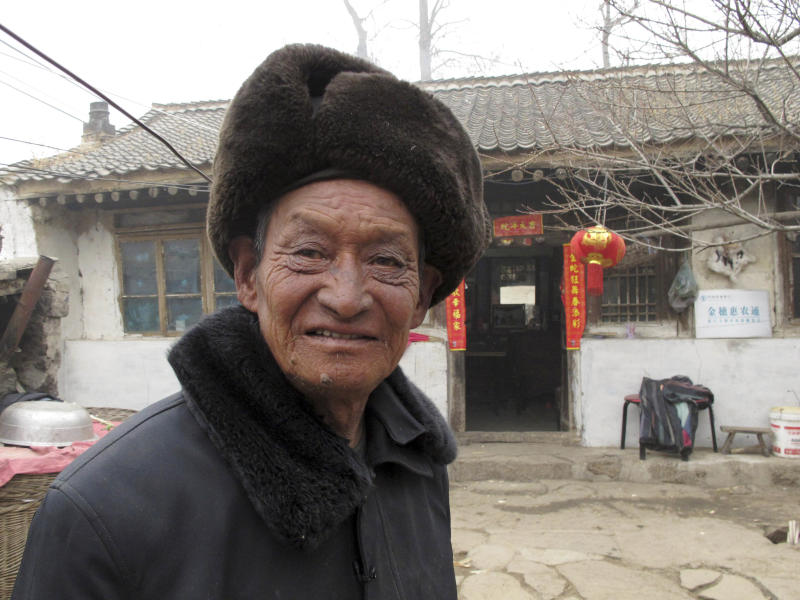 In this photo taken Monday, Feb. 25, 2013, corn farmer Tang Rongbin stands outside his home in Luotuowan village in northern China's Hebei province. Chinese leader Xi Jinping visited Tang in December 2012 as part of efforts to style himself as a no-frills man-of-the-people. Xi has also presented himself as an economic reformer and an iron-fisted graft-buster, spurring expectations for change, but as he prepares to be appointed president, pressure will be growing on him to deliver. (AP Photo/Gillian Wong)