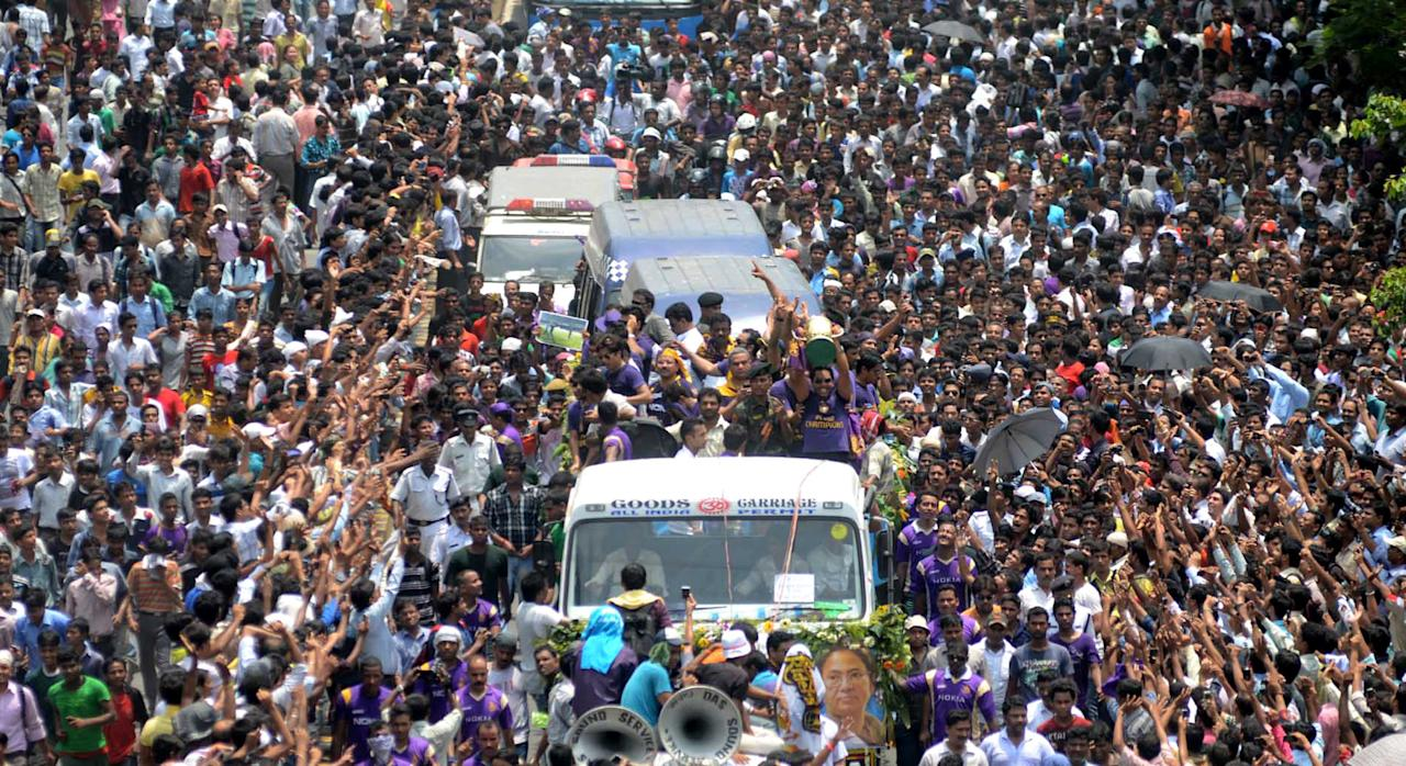 Kolkata Knight Riders players and officials ride on a truck with the tournament trophy during a victory procession to the Eden Gardens in Kolkata on May 29, 2012, following their victory in this year's IPL Twenty20 cricket tournament. Kolkata Knight Riders claimed victory in the annual IPL Twenty20 cricket tournament final on May 27, beating defending champions Chennai Super Kings by five wickets.