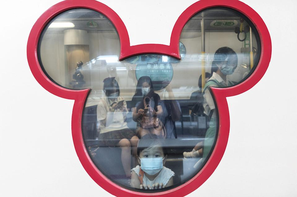 This image shows a child peering through a window shaped like Mickey Mouse.