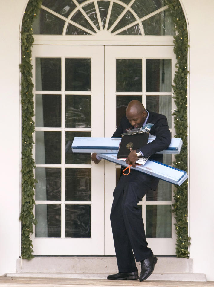 U.S. President Barack Obama's personal assistant Reggie Love tries to open a door with two boxes in his hands after returning with Obama from a Home Depot in Virginia, at the White House in Washington December 15, 2009.  REUTERS/Larry Downing  (UNITED STATES - Tags: POLITICS)