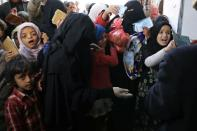 People, including children, gather outside a charity kitchen to get food donations in Sanaa