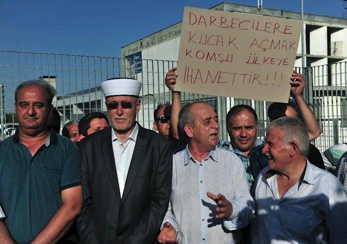 Members of the Muslim minority of Thrace, northern Greece, demonstrate outside of the airport of Alexandroupolis on July 16, 2016, demanding the Greek government hand over to Turkey the eight Turkish officers seeking asylum after a coup bid (AFP Photo/Sakis Mitrolidis)