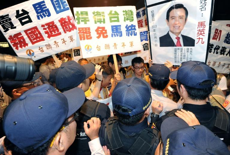 Pro-independence activists from the Taiwan Solidarity Union (TSU), holding a portrait of President Ma Ying-jeou, clash with police at Taoyuan airport, on November 8, 2015