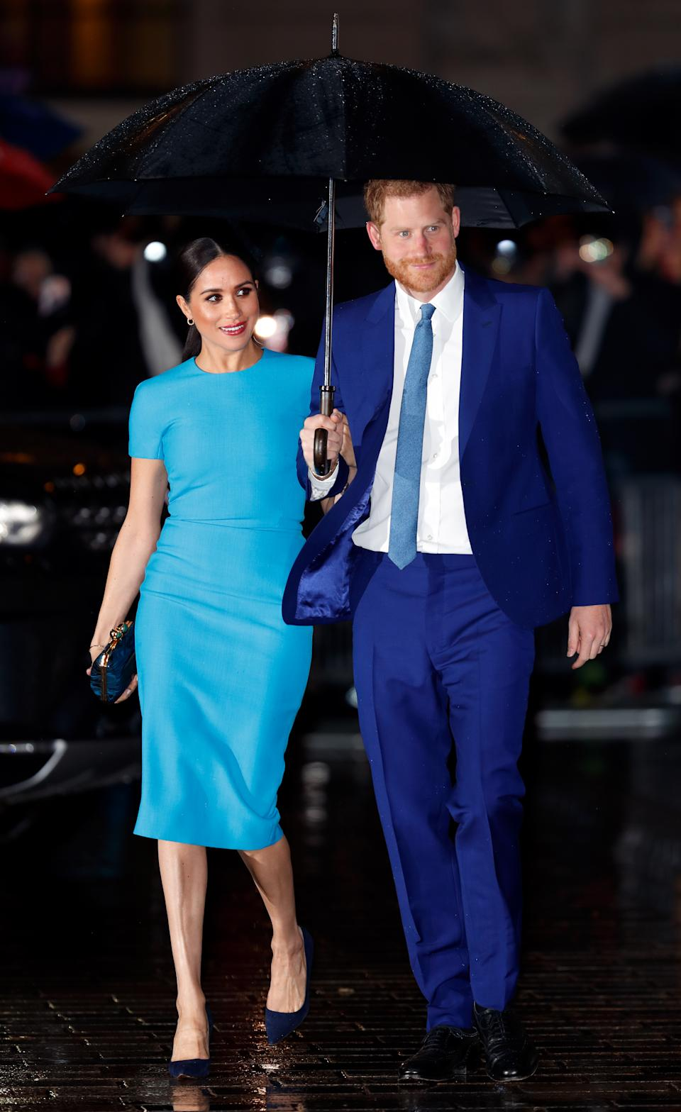 Prince Harry holds an umbrella over himself and Meghan Markle
