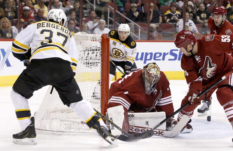 Boston Bruins' Patrice Bergeron (37) scores a goal against Phoenix Coyotes' Mike Smith, third from the left, as Coyotes' Derek Morris (53) defends and Coyotes' Keith Yandle, back right, and Bruins' Brad Marchand (63) look on during the first period of an NHL hockey game on Saturday, March 22, 2014, in Glendale, Ariz. (AP Photo/Ross D. Franklin)