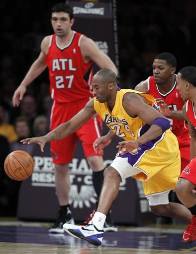 Los Angeles Lakers guard Kobe Bryant (24) retrieves the ball after it was knocked away, as Atlanta Hawks' Jeff Teague, right, and Joe Johnson, second from right, and center Zaza Pachulia (27) defend during the first half of an NBA basketball game in Los Angeles, Tuesday, Feb. 14, 2012. (AP Photo/Alex Gallardo)