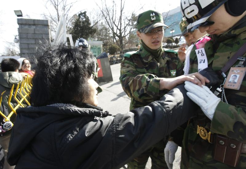 A South Korean anti-war protester gives a flower to an army soldier during a rally against South Korean activists who  launched propaganda leaflets toward North Korea, at a main gate of Defense Ministry in Seoul, South Korea, Wednesday, March 2, 2011. South Korean activists say they will continue launching propaganda leaflets toward North Korea despite Pyongyang's threats to fire at South Korean border towns in retaliation.(AP Photo/Ahn Young-joon)