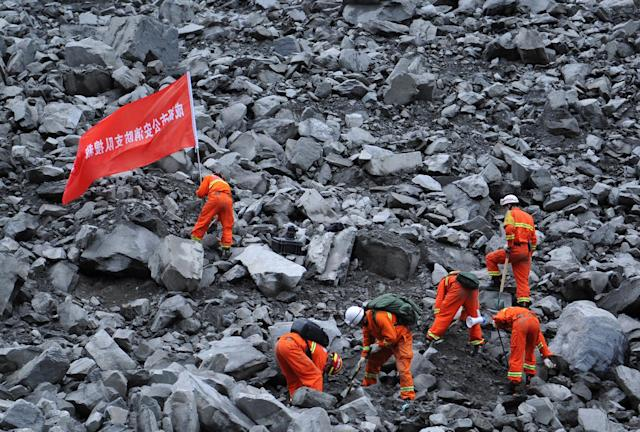 """<p>Rescue workers search for survivors at the site of a landslide that occurred in Xinmo Village, Mao County, Sichuan province, China, June 24, 2017. The writing on the flag reads: """"Chengdu Fire Departmant Rescue Team"""". (Photo: Stringer/Reuters) </p>"""