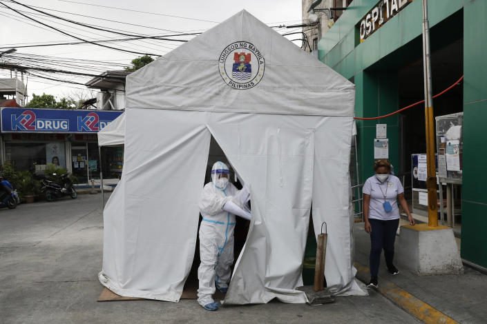 A health worker wearing a protective suit goes out of a tent with COVID-19 patients outside a hospital in Manila, Philippines on Monday, April 26, 2021. COVID-19 infections in the Philippines surged past 1 million Monday in the latest grim milestone as officials assessed whether to extend a monthlong lockdown in Manila and outlying provinces amid a deadly spike or relax it to fight recession, joblessness and hunger. (AP Photo/Aaron Favila)
