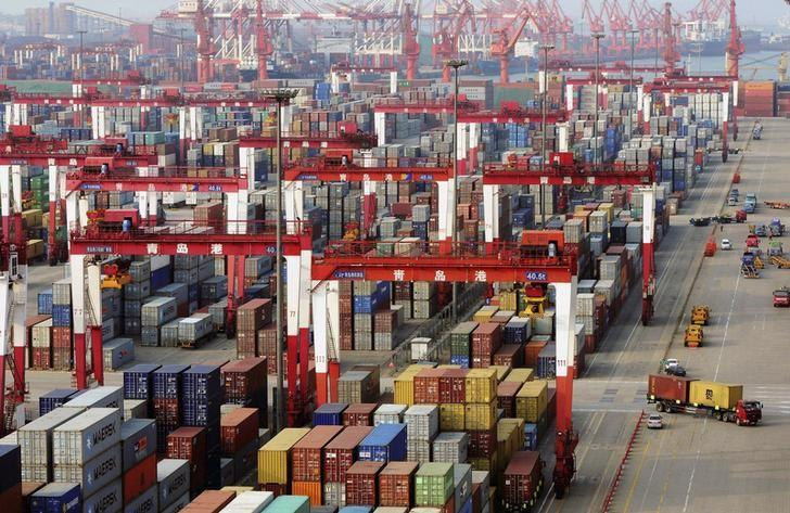 Trucks drive past piles of shipping containers at the Qingdao port in Qingdao
