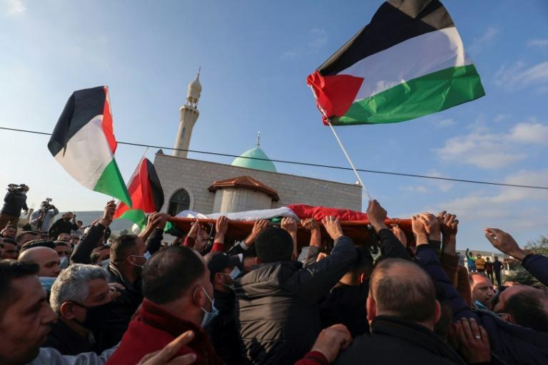 Mourners carry the body of Palestinian Atef Yussef Hanaysheh, who was shot dead by Israeli soldiers when clashes erupted during a demonstration, in the village of Beit Dajan in the Israeli-occupied West Bank on March 19