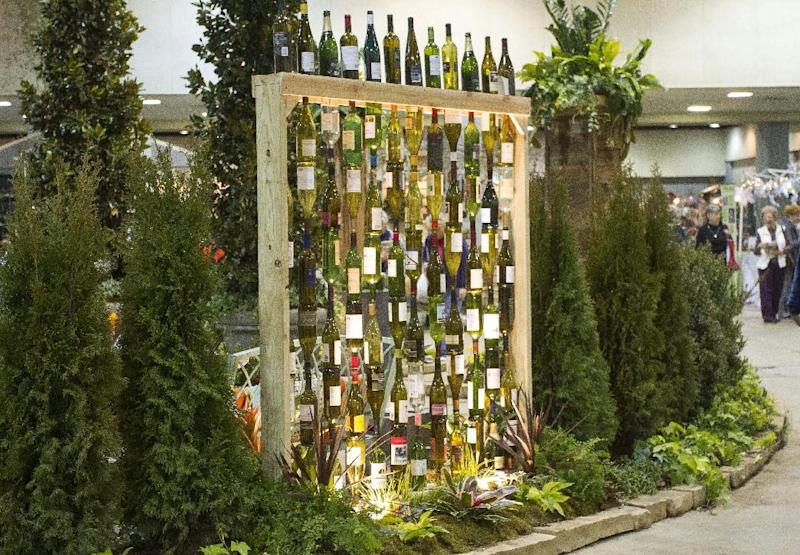 """In this publicity photo provided by Chris H. Olsen, the Landscape Designer, Olsen, of Little Rock, Ark., created a decorative wall out of empty wine bottles by threading them onto metal poles inserted into a wooden frame. Olsen shares outdoor decorating ideas in his book """"Chris H. Olsen's Five Seasons"""" (Leisure Arts, 2011). (AP Photo/Chris H. Olsen, Janet Warlick/Camera Work)"""