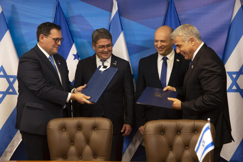 Israeli Prime Minister Naftali Bennett, second right, and Honduran President Juan Orlando Hernandez, second left, look on as Israeli Foreign Minister Yair Lapid, right, and Honduran Foreign Minister Lisandro Rosales exchange signed agreements between their two countries at the prime minister's office, in Jerusalem, Thursday, June 24, 2021. (Heidi Levine/Pool via AP).