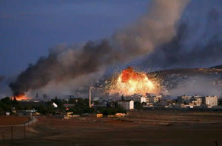 Smoke and flames rise over Syrian town of Kobani after an airstrike, as seen from the Mursitpinar crossing on the Turkish-Syrian border in the southeastern town of Suruc in Sanliurfa province, October 20, 2014. REUTERS/Kai Pfaffenbach