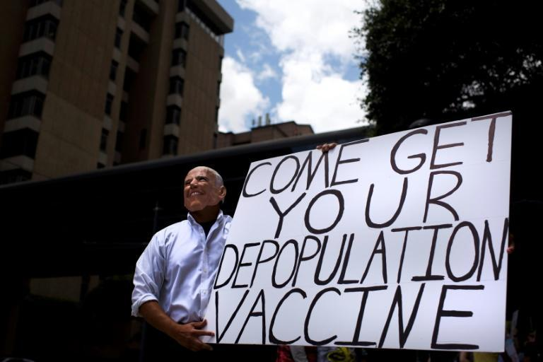 An anti-vaccine protester dressed up as Joe Biden in June 2021 promoted one of several conspiracies that have contributed to low vaccination rates, particulary among US Republicans