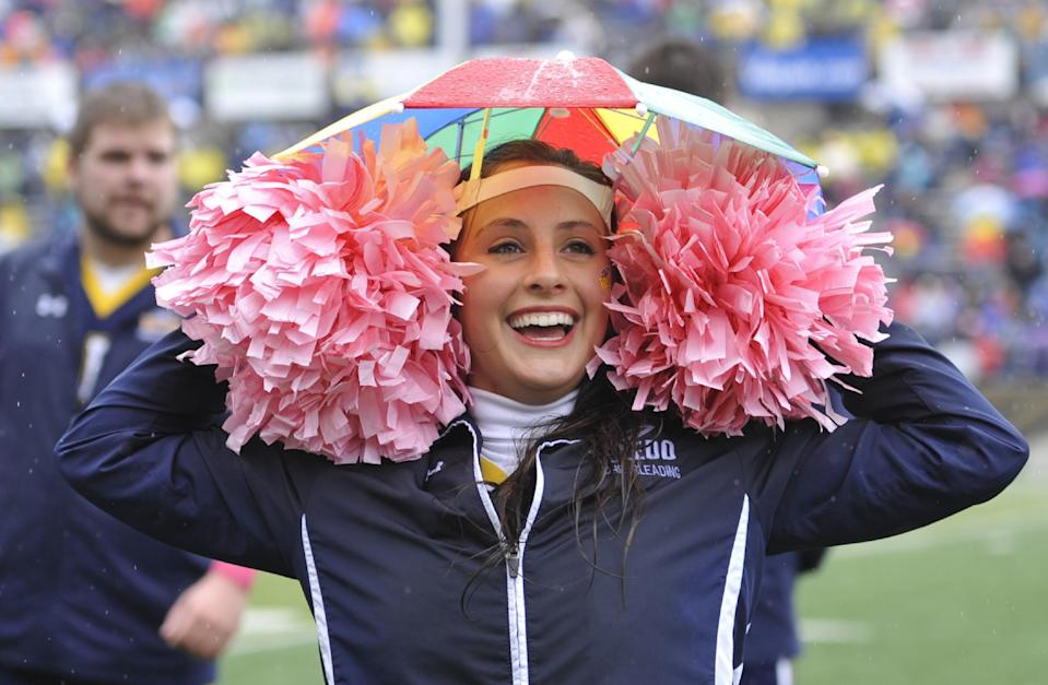 Toledo cheerleader Alysa Malcolm puts on an umbrella hat during the second quarter of an NCAA college football game between Toledo and Navy in Toledo, Ohio, Saturday, Oct. 19, 2013. (AP Photo/David Richard)