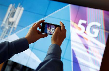 FILE PHOTO: A journalist uses his mobile phone to take a picture of the 5G logo prior to the auction of spectrum for 5G services at the Bundesnetzagentur head quarters in Mainz