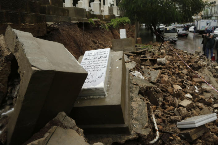 CORRECTS TO CAPITAL'S ONLY JEWISH CEMETERY, NOT COUNTRY'S - Graves in a Jewish cemetery sit damaged from heavy rains in the Sodeco area of Beirut, Lebanon, Thursday, Dec. 26, 2019. A heavy storm hit Lebanon with heavy rain and strong winds causing an old wall to collapse in the capital's only Jewish cemetery, causing damage to several tombstones. Lebanon once had a thriving Jewish community, but the various Arab-Israeli wars and Lebanon's own 1975-90 civil war caused waves of emigration and almost none are left in the country today. (AP Photo/Hassan Ammar)