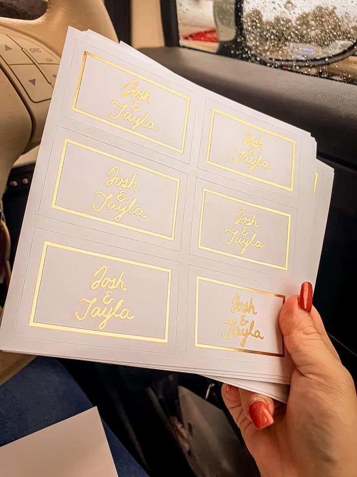 Woman's hand holding sheets of white labels that read 'Josh & Tayla' in gold pen