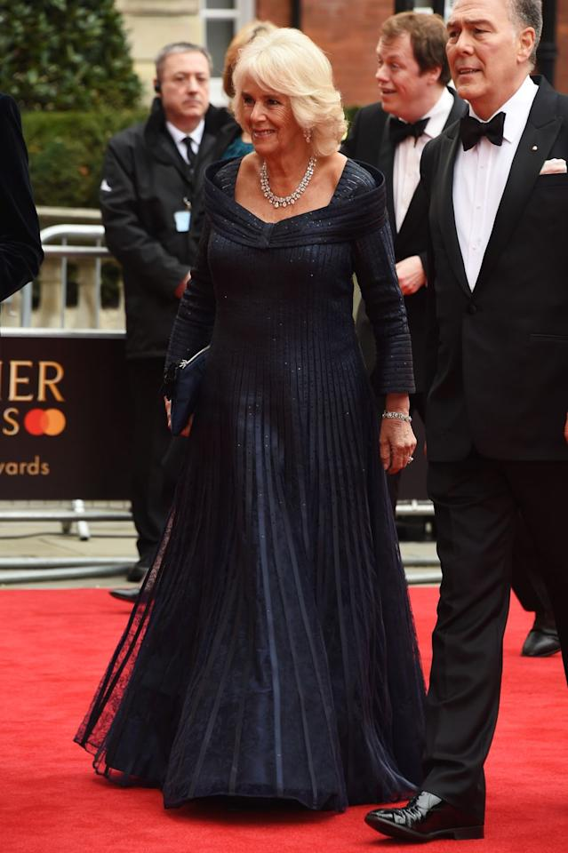 """<p>Camilla arrived at the 2019 Olivier Awards re-wearing the sparkly navy gown, diamond statement necklace, and diamond earrings that she originally wore to <a href=""""https://www.townandcountrymag.com/society/tradition/g25058013/prince-charles-70th-birthday-party-photos/"""" target=""""_blank"""">Prince Charles's 70th birthday party. </a></p>"""