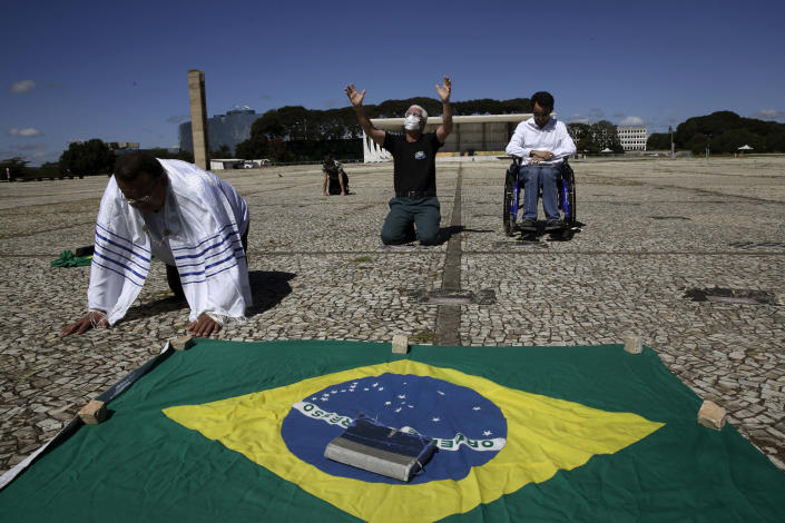 Evangelicals from the Fountain of Faith church pray for Brazil's President Jair Bolsonaro outside Planalto presidential palace in Brasilia, Brazil, Tuesday, April 28, 2020. Brazil's Supreme Court on Monday night authorized an investigation into whether Bolsonaro committed crimes by allegedly attempting to interfere with the country's Federal Police. (AP Photo/Eraldo Peres)