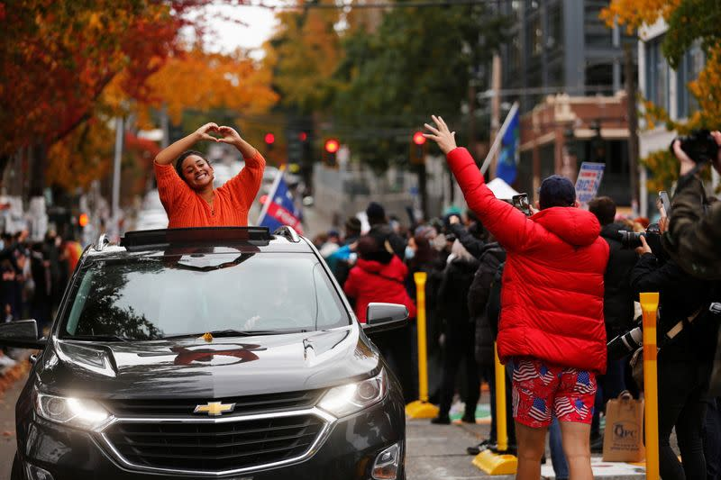 Nadine Gibson gestures from a car after the media announced that Democratic U.S. presidential nominee Joe Biden has won the 2020 U.S. presidential election, in Seattle
