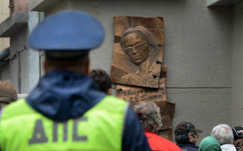 People look at a plaque commemorating slain anti-Kremlin reporter Anna Politkovskaya in Moscow