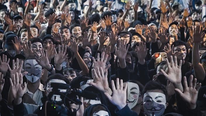 """Protesters adopted the motto """"Five demands, not one less!"""" and wore masks in defiance of Carrie Lam plan to invoke colonial-era emergency powers to ban masks"""