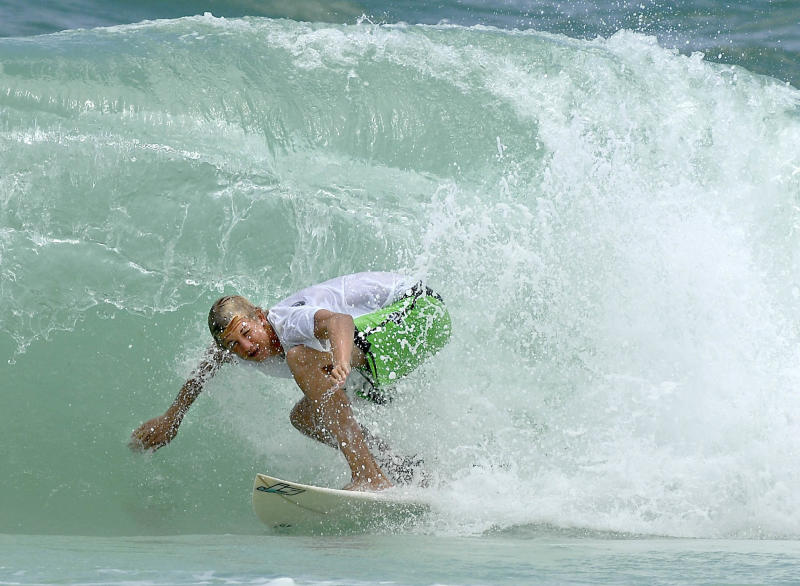 A surfer rides a wave off Okaloosa Island in Fort Walton Beach, Fla., on Saturday, June 23, 2012. A storm system will bring more heavy showers and thunderstorms to southern Florida and the Gulf Coast. This system has a high chance of tropical cyclone development over the weekend. (AP Photo/Northwest Florida Daily News, Nick Tomecek)