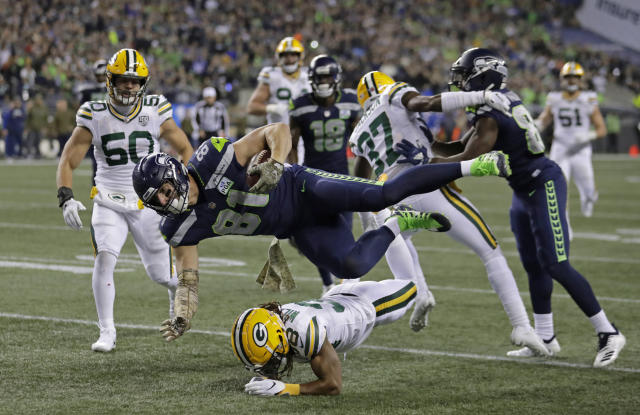 Seattle Seahawks tight end Nick Vannett (81) gets horizontal above Green Bay Packers cornerback Tramon Williams, lower-center, as Vannett carries the ball just short of the goal line against the Green Bay Packers during the first half of an NFL football game, Thursday, Nov. 15, 2018, in Seattle. (AP Photo/Stephen Brashear)
