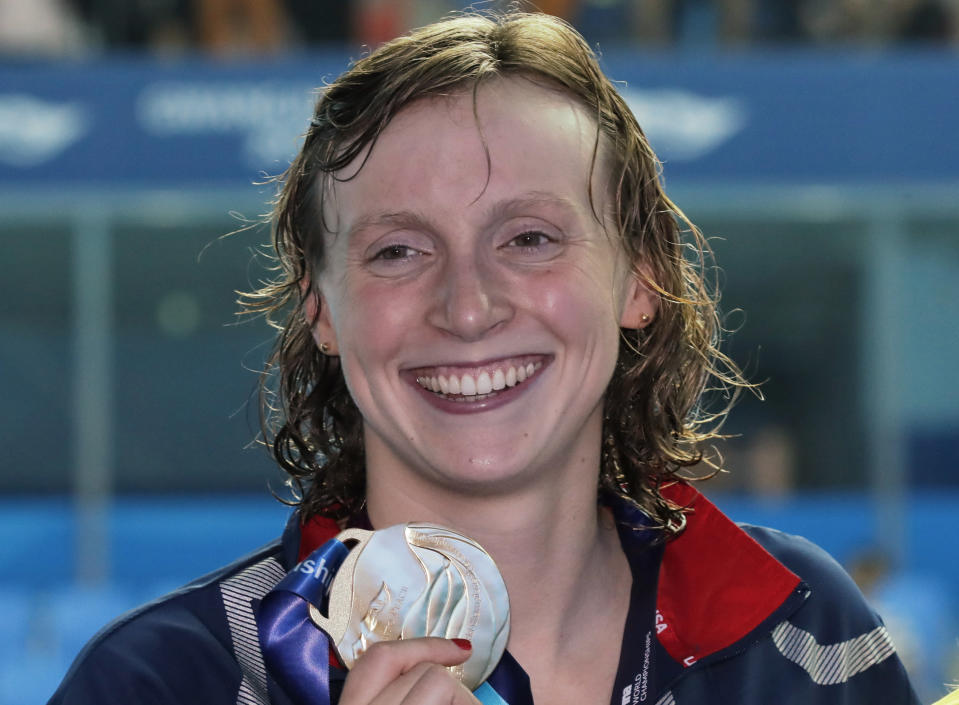 File-This July 27, 2019, file photo shows gold medalist United States' Katie Ledecky posing with her medal following the women's 800m freestyle final at the World Swimming Championships in Gwangju, South Korea. Like everyone else, Ledecky was forced to shelve her plans when the coronavirus pandemic took hold. Instead of looking far into the future, the five-time Olympic champion swimmer switched to a more immediate mindset. Forget that the four-year cycle leading to the 2024 Paris Olympics is already underway. Ledecky is still working toward making a big splash at this summer's delayed Tokyo Games.(AP Photo/Lee Jin-man, File)