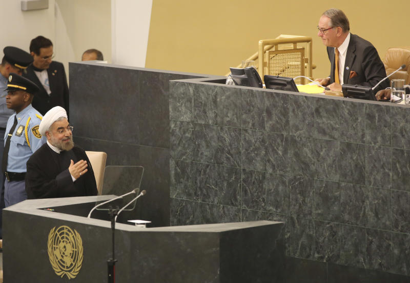 Iranian President Hasan Rouhani, left, arrives to addresses the 68th session of the United Nations General Assembly, Tuesday, Sept. 24, 2013 at U.N. headquarters. (AP Photo/Mary Altaffer)