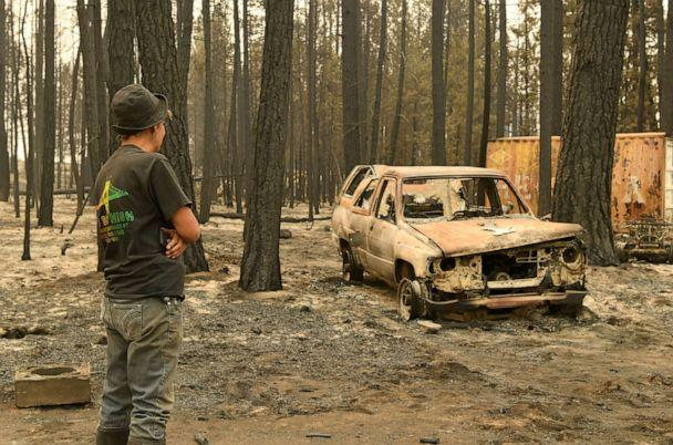 PHOTO: Pam Brown observes a burnt out truck on her friend's property after it was destroyed by the Bootleg Fire, in Sycan Estates, Ore., July 24, 2021. (Mathieu Lewis-Rolland/Reuters)