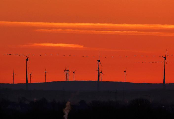 """<p>A flock of birds flies past wind turbines just before sunrise in the outskirts of Frankfurt, Germany on March 28, 2017. A senior EU official says Wednesday, May 31, 2017, the EU and China will reaffirm their commitment to the Paris climate change accord this week, regardless of whether President Donald Trump pulls out of the pact. The official told reporters that the EU and China will also """"spell out"""" how they plan to meet their commitments to the accord at talks in Brussels on Friday. (AP Photo/Michael Probst) </p>"""