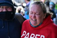 A woman reacts to pepper spray deployed by police at a Get Out The Vote march in Graham