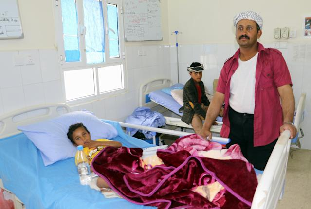 <p>A Yemeni man stands next to the bed of his child, wounded in an air strike by coalition forces the previous day on a bus at a market in rebel-held northern Yemen, at a hospital in the Yemeni city of Saada on Aug. 10, 2018. (Photo: Stringer/AFP/Getty Images) </p>