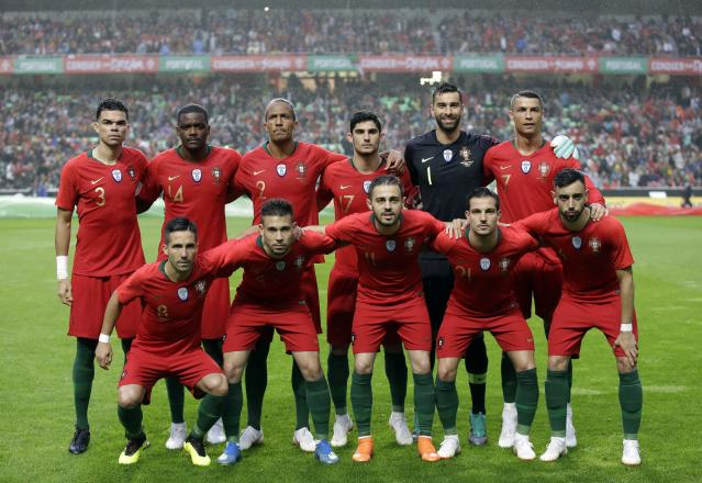 In this photo taken on Thursday, June 7, 2018, Portugal players pose for photos before a friendly soccer match between Portugal and Algeria in Lisbon, Portugal. Players are, from left to right, front row, Pepe, William Carvalho, Bruno Alves, Goncalo Guedes, goalkeeper Rui Patricio and team captain Cristiano Ronaldo. And on front row, Joao Moutinho, Raphael Guerreiro, Bernardo Silva, Cedric Soares and Bruno Fernandes. (AP Photo/Armando Franca)