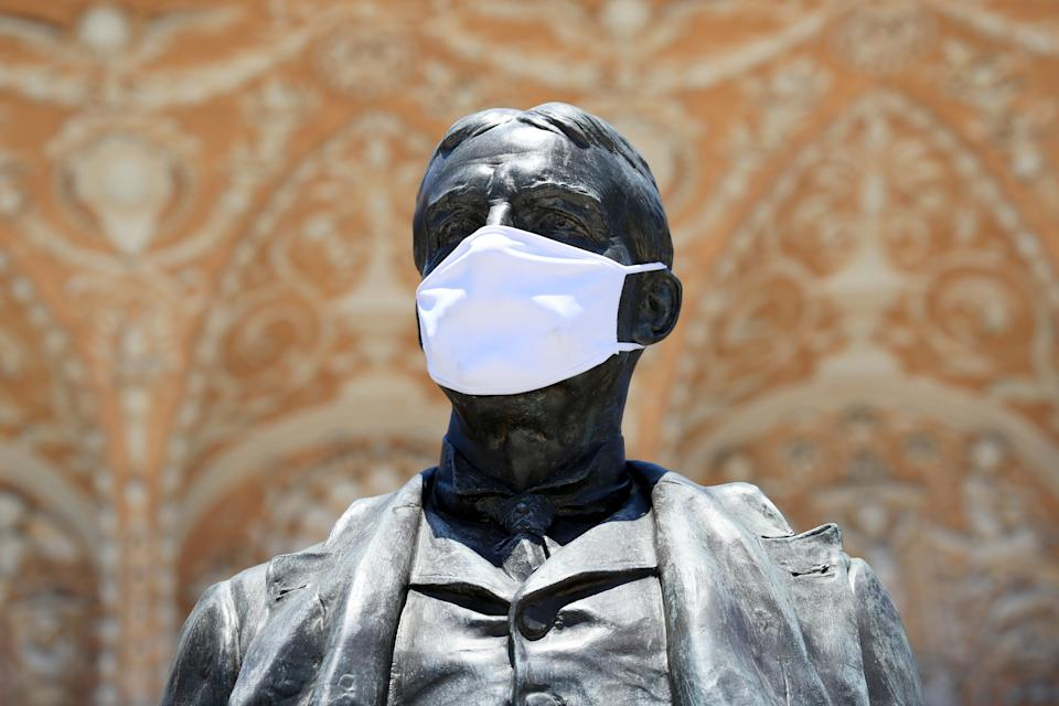 SAINT AUGUSTINE, FLORIDA - MAY 04: A mask is seen on the statue of Henry M. Flagler as the state of Florida enters phase one of the plan to reopen the state on May 04, 2020 in Saint Augustine, Florida. Restaurants, retailers, beaches and some state parks reopen today with caveats, as the state continues to ease restrictions put in place to contain the coronavirus (COVID-19). (Photo by Sam Greenwood/Getty Images)