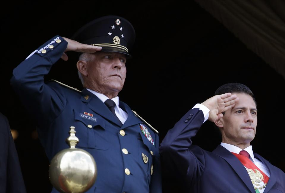 FILE - In this Sept. 16, 2016 file photo, Defense Secretary Gen. Salvador Cienfuegos, left, and Mexico's President Enrique Pena Nieto, salute during the annual Independence Day military parade in Mexico City's main square. Mexico's top diplomat says the country's former defense secretary, Gen. Salvador Cienfuegos, has been arrested in Los Angeles. Foreign Relations Secretary Marcelo Ebrard wrote Thursday, Oct. 15, 2020 in his Twitter account that U.S. Ambassador Christopher Landau had informed him of Cienfuegos' arrest. (AP Photo/Rebecca Blackwell, File)