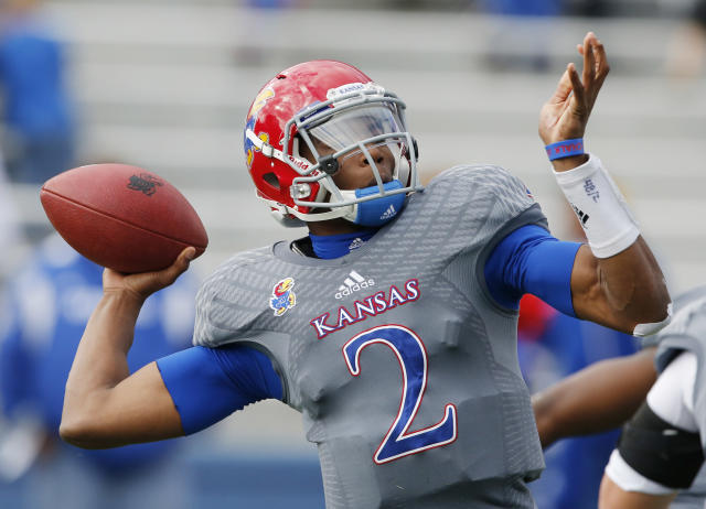 Kansas quarterback Montell Cozart (2) passes to a teammate during the first half of an NCAA college football game against West Virginia at Kansas Memorial Stadium in Lawrence, Kan., Saturday, Nov. 16, 2013. (AP Photo/Orlin Wagner)