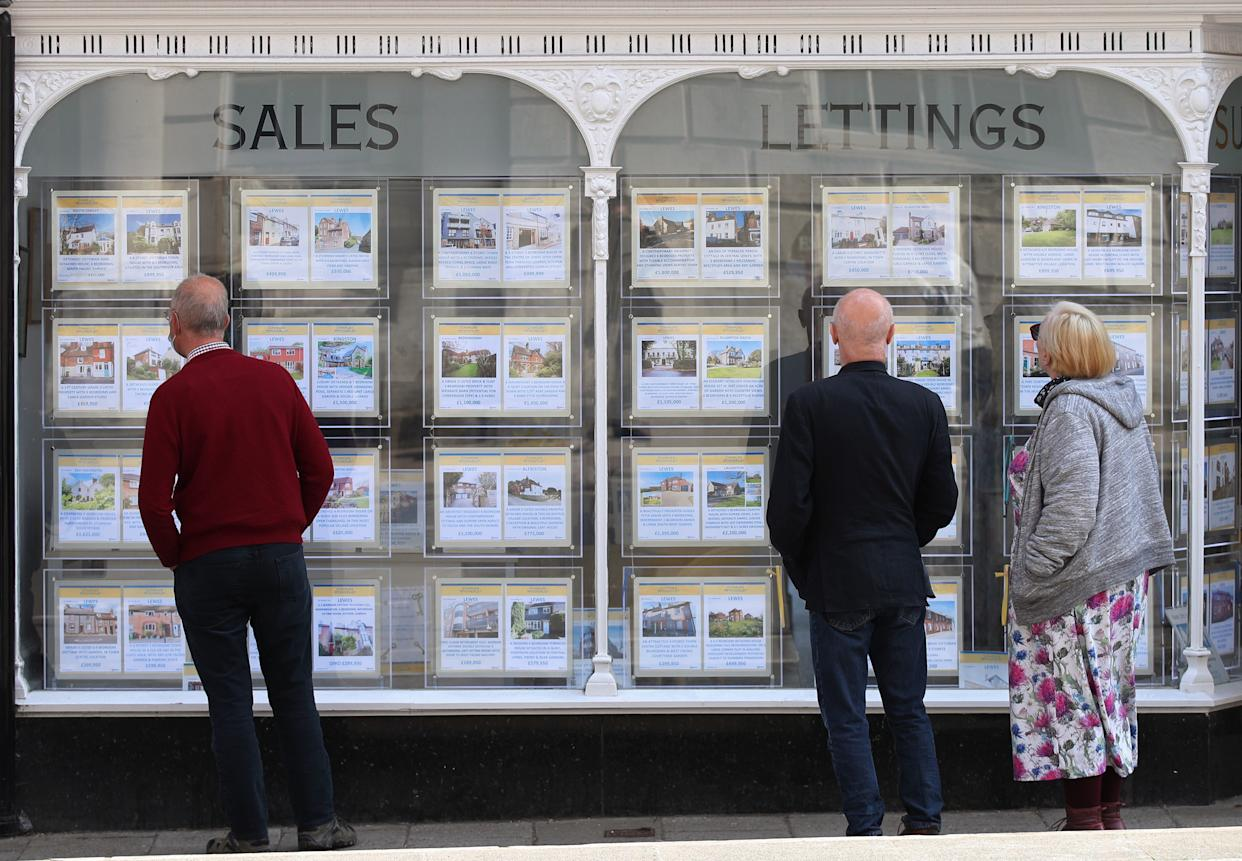 File photo dated 21/04/21 of people looking at house price signs displayed in the window of an estate agents. This year's housing market is on course to be the busiest since 2007, according to a property website. Issue date: Wednesday May 26, 2021.