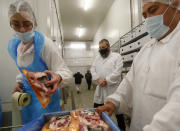 An Orthodox rabbi, centre, looks at workers packing Kosher poultry meat in a Kosher slaughterhouse in Csengele, Hungary on Jan. 15, 2021. Hungarian Jewish community, exporter of Kosher meat, fear that the European Court of Justice verdict on upholding a Belgian law that banned ritual slaughter could have an affect on other EU member states' regulation on Kosher slaughter. Animal rights groups that pushed for the Flanders law argue that ritual slaughter without stunning amounts to animal cruelty. (AP Photo/Laszlo Balogh)