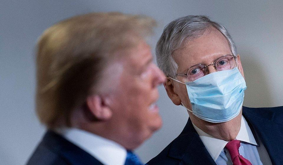 Mitch McConnell listens to Donald Trump speak during a press conference in Washington last year. Photo: AFP