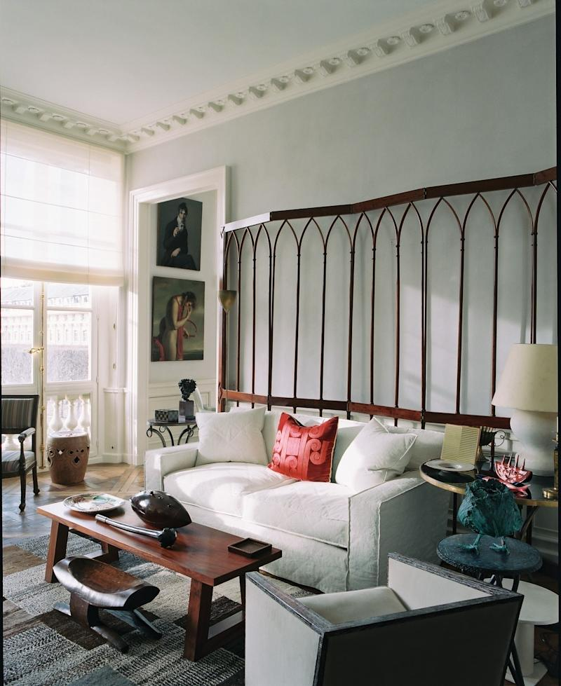 In the living room, a 19th-century French screen stands behind the sofa.