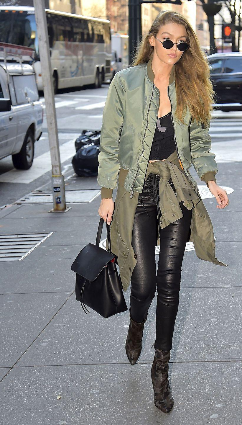<p>In an army green satin bomber jacket, black crop top, cargo jacket tied around the waist, leather pants, camo boots, Mansur Gavriel bag and rounded sunglasses while out in New York.</p>