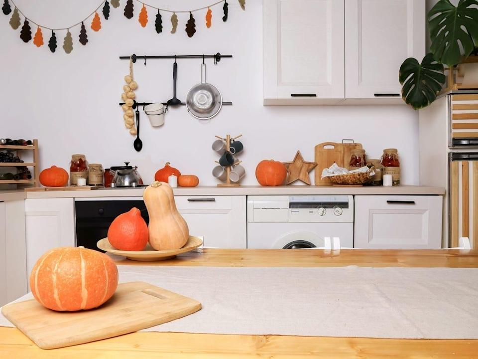 A kitchen with seasonal decor like pumpkins, gourds, and garland.