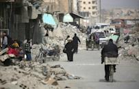 Syrians walk amidst destroyed buildings in Raqa in January 2018 after a huge military ground operation by Kurdish fighters and in the air by US warplanes defeated jihadists from the Islamic State group but left the city completely disfigured