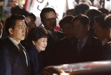 South Korea's ousted leader Park Geun-hye greets her supporters as she arrives at her private home in Seoul