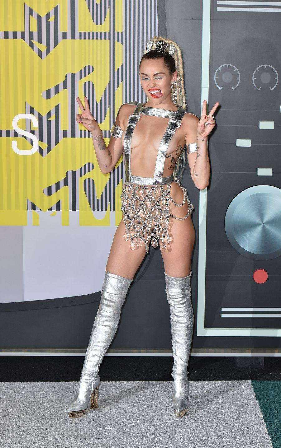 """<p>As the host of the 2015 VMAs, Miley Cyrus had <a href=""""https://www.harpersbazaar.com/celebrity/red-carpet-dresses/news/g6143/miley-cyrus-vma-fashion/"""" rel=""""nofollow noopener"""" target=""""_blank"""" data-ylk=""""slk:several outlandish outfits"""" class=""""link rapid-noclick-resp"""">several outlandish outfits</a> she wore throughout the evening. This <a href=""""https://people.com/style/vmas-2015-miley-cyrus-opts-for-silver-suspenders-and-nothing-else-for-first-look-of-the-night/"""" rel=""""nofollow noopener"""" target=""""_blank"""" data-ylk=""""slk:dress"""" class=""""link rapid-noclick-resp"""">dress </a>(if you can call it that) by Atelier Versace was her first ensemble of the night. </p>"""